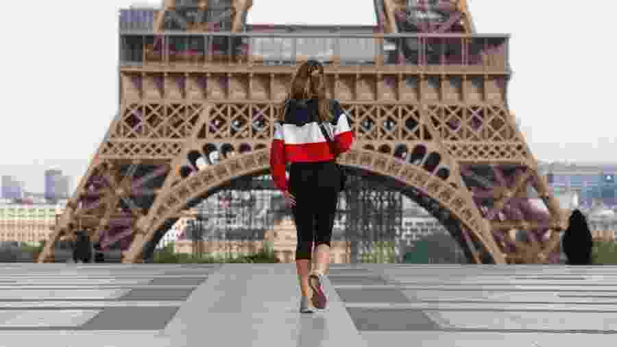 Mulher em frente à Torre Eiffel em Paris durante a pandemia do novo coronavírus - Mehdi Taamallah/NurPhoto via Getty Images