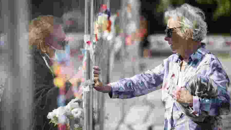 3/6/2020 - Mulheres conversam separadas por cerca na fronteira entre Eslovênia e Itália durante a pandemia do novo coronavírus - Jure Makovec/AFP