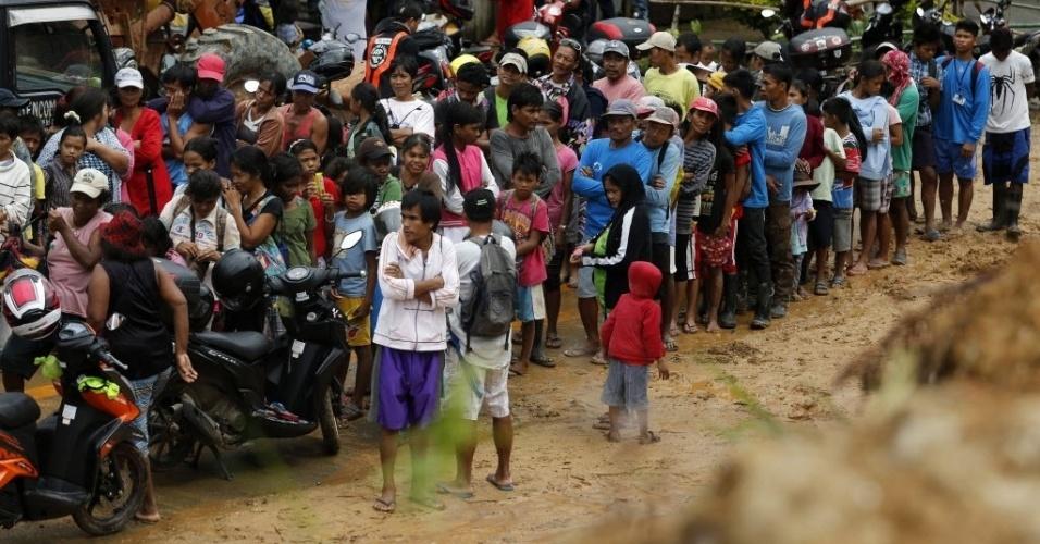 31.jan.2016 - Filipinos afetados por um deslizamento de terra na cidade de Infanta recebem ajuda de um grupo de motociclistas, neste domingo (31). Centenas de voluntários levaram comida e água para os moradores e pediram ao governo que limpe as estradas para facilitar a operação