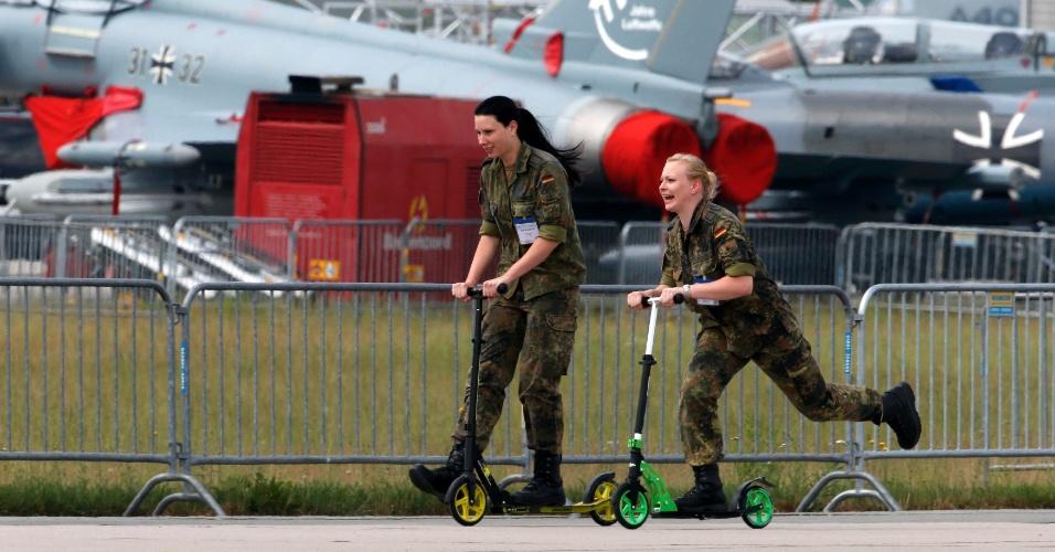 31.mai.2016 - Mulheres das forças armadas alemãs andam de patinete no aeroporto de Schoenefeld, próximo a Berlim, na Alemanha, onde será realizado o International Aerospace Exhibition (ILA) Berlin Air Show, de 1º a 4 de junho