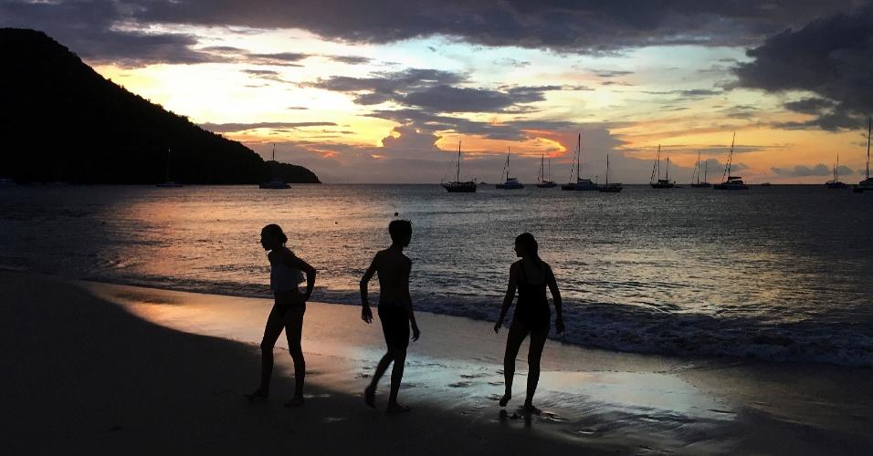 24.nov.2016 - Jovens brincam na água na praia da baía de Rodney após o pôr do sol no Gros Islet, nos EUA