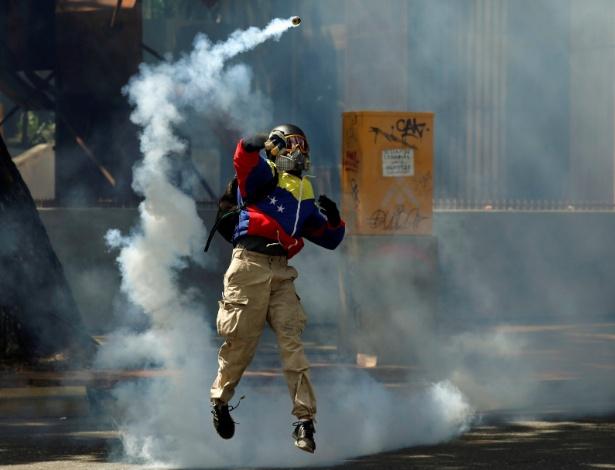 Vestindo jaqueta com as cores da bandeira da Venezuela, manifestante joga gás lacrimogêneo durante confronto com a polícia em protesto em Caracas