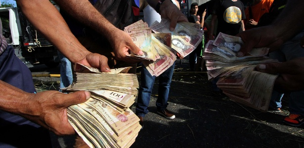 Venezuelanos mostram maços com notas de 100 bolívares em protesto em San Cristobal