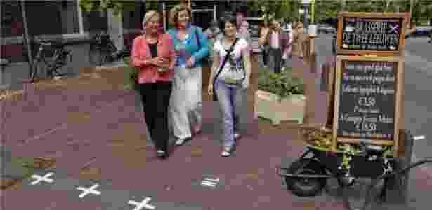 As fronteiras são marcadas por cruzes brancas nas calçadas, indicando 'NL' de um lado e 'B' no outro - Toerisme Baarle - Toerisme Baarle