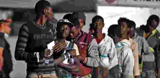 Africanos deixam embarcação - AFP PHOTO / Giovanni ISOLINO - AFP PHOTO / Giovanni ISOLINO