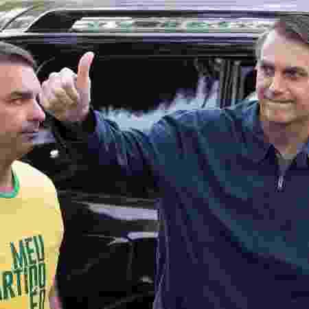 7.out.2018 - Flavio e Jair Bolsonaro durante votação  no Rio - Fernando Souza/AFP