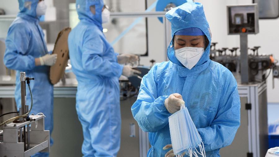 11/03/2020 - Uma funcionária analisa máscaras de proteção ao coronavírus em Beijing na China  - Xinhua/Ren Chao