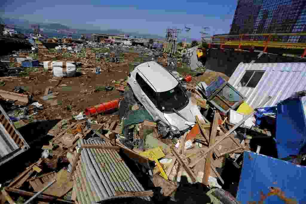 17.set.2015 - Carro destruído fica entre destroços de casas após terremoto de magnitude 8,3 atingir a cidade de Coquimbo, a 445 km de Santiago, no Chile. Mais de um milhão de pessoas foram retiradas de suas casas após o tremor na costa chilena no oceano Pacífico, que provocou ondas fortes em cidades litorâneas. O epicentro do tremor foi a cerca de 55 km a oeste de Illapel. Ele ocorreu por volta de 19h54 e teve uma profundidade de 33 km - Ivan Alvarado/Reuters