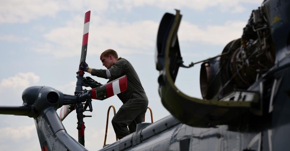 30.mai.2016 - Soldado das forças armadas da Alemanha inspeciona o motor de um helicóptero para o International Aerospace Exhibition (ILA), no aeroporto de Schoenefeld, próximo a Berlim, na Alemanha