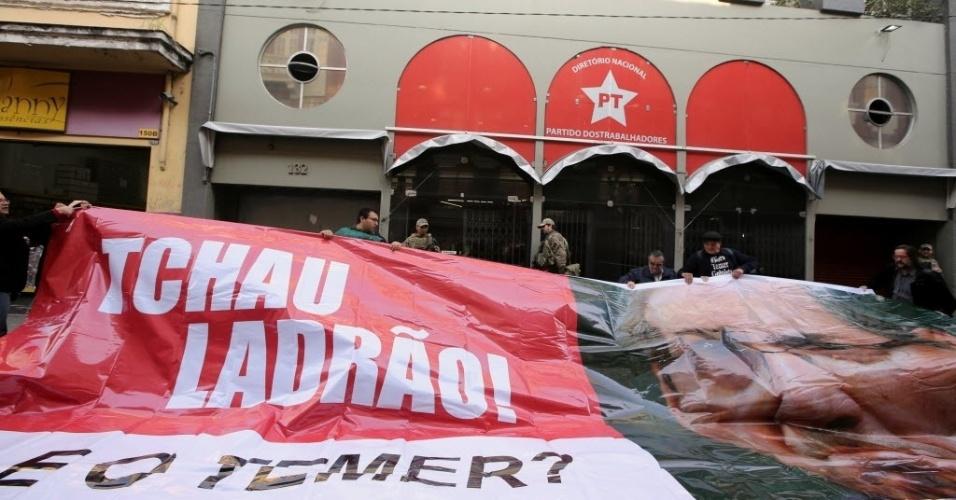 """23.jun.2016 - Um grupo de membros do diretório do PT (Partido dos Trabalhadores) e integrantes de movimentos sociais protestaram em frente à sede do partido, na região central de São Paulo, onde a Polícia Federal cumpria um mandado de busca e apreensão. Os manifestantes estenderam uma faixa com a foto do presidente afastado da Câmara dos Deputados, Eduardo Cunha (PMDB-RJ), e os dizeres """"Tchau, ladrão. E o Temer?"""""""
