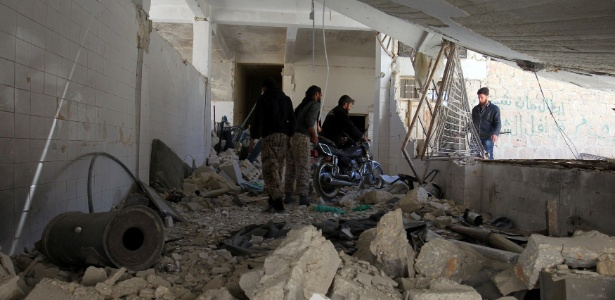 5.abr.2017 - Homens observam os escombros de um posto médico bombardeado em Khan Sheikhoun após o ataque químico