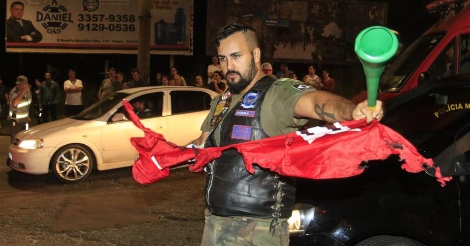 7.abr.2018 - Manifestante anti-Lula rasga bandeira do PT em frente à sede da PF em Curitiba