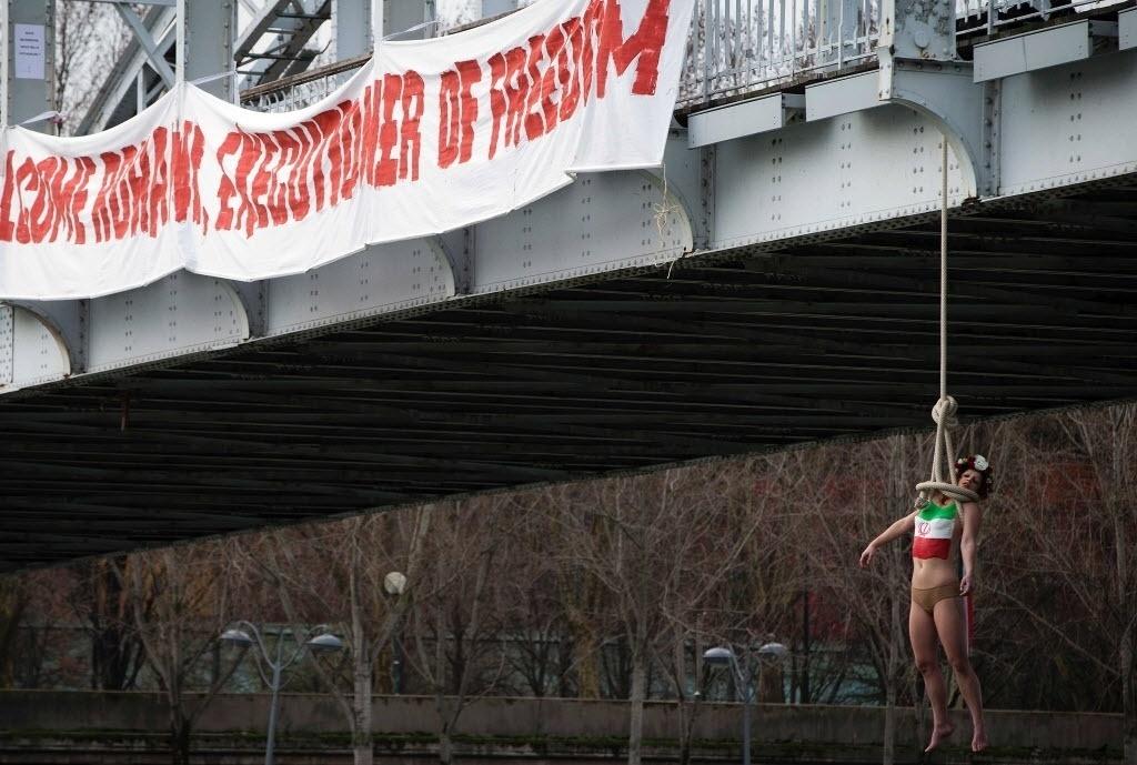 28.jan.2016 - A organização feminista Femen recebeu o presidente iraniano, Hassan Rohani, com um enforcamento simbólico de uma de suas ativistas que fazia topless e tinha a bandeira iraniana pintada no peito em Paris, na França. O grupo afirmou que a intenção é denunciar a situação dos direitos humanos no Irã e dar as boas-vindas ao