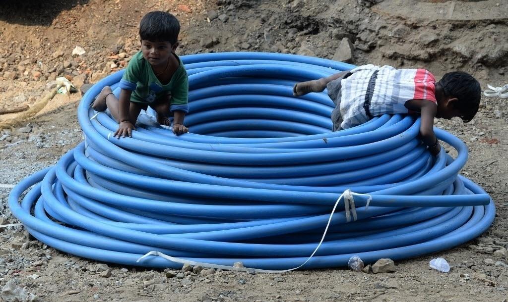 29.fev.2016 - Irmãos desabrigados brincam com tubulação em estrada de Bombaim, na Índia