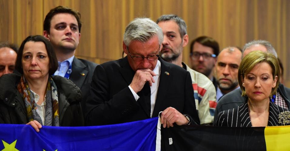 23.mar.2016 - Funcionários da Comissão Europeia se emocionam segurando a bandeira da União Europeia e da Bélgica durante homenagem oficial às vítimas de ataques em Bruxelas