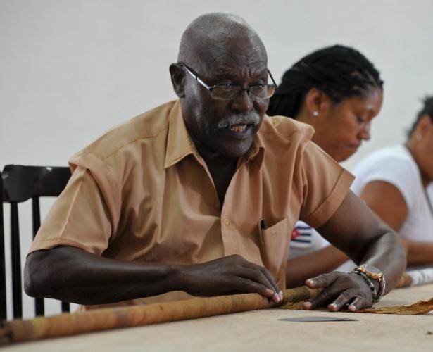 11.ago.2016 - O 'enrolador' de charutos cubanos Jose Castelar Cairo, conhecido como 'Cueto', enrola um novo cigarro gigante em Havana