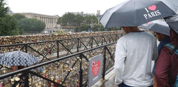 """Turistas observam placa que diz """"nossas pontes não resistirão ao seu amor"""", na Pont Neuf, em Paris"""