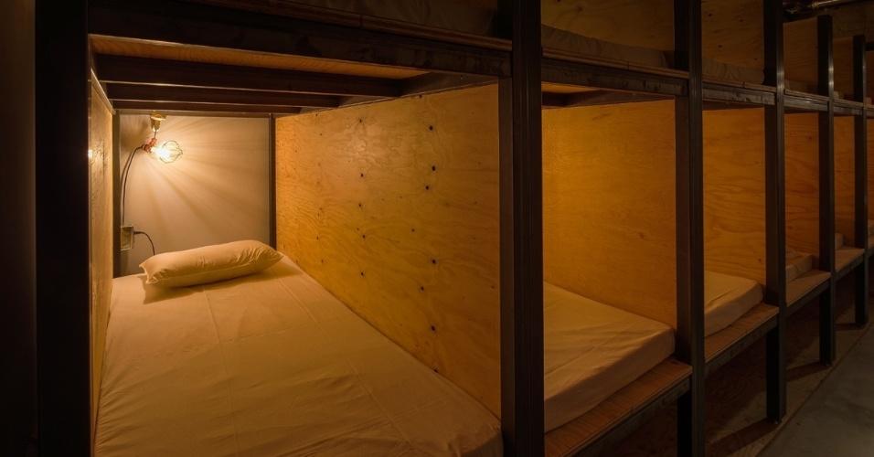 """05.set.2016 - O espaço conta com 30 camas, sendo 18 delas em formato de beliche. Todas ficam atrás das estantes de livros, que funcionam como as paredes de um quarto. Uma vez que o hóspede """"adentra"""" a estante, pode usufruir de um colchão, travesseiro, luz de cabeceira e tomadas para seu laptop, por exemplo. O wi-fi é grátis"""