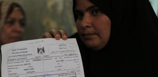 """Paciente palestina exibe documento escrito """"Estado da Palestina"""" fornecido pelo departamento de saúde controlado pelo Hamas, na Cidade de Gaza"""