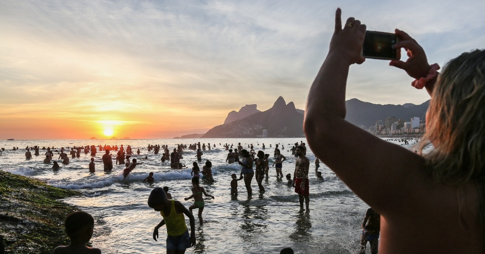 27.dez.2016 - Mulher tira foto do pôr do sol com o celular na praia de Ipanema, na zona sul do Rio de Janeiro, ainda lotada