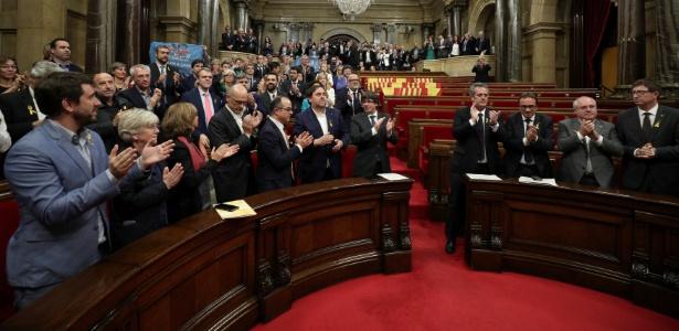 O presidente catalão Carles Puigdemont e deputados aplaudem o resultado da votação do Parlament, que aprovou uma resolução para a declaração da independência da região