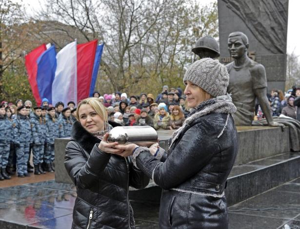 Veteranos da juventude comunista, a Komsomol, mostram a capsula do tempo durante a cerimônia de abertura, em Cherepovets, na Rússia