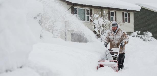 Homem tenta remover neve da calçada depois de dois dias de neve em Erie, Pensilvânia