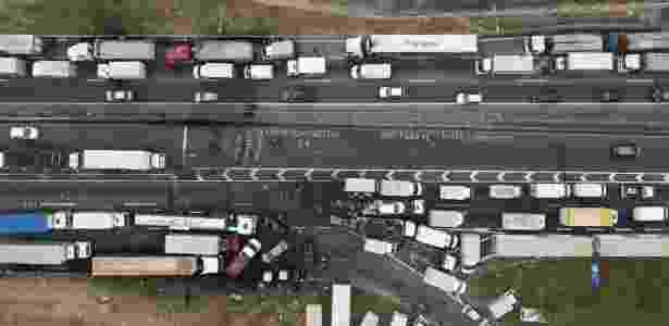 Caminhões permanecem neste sábado (26) enfileirados na rodovia Régis Bittencourt, nas imediações de Embu das Artes (SP) - Danilo Verpa/Folhapress