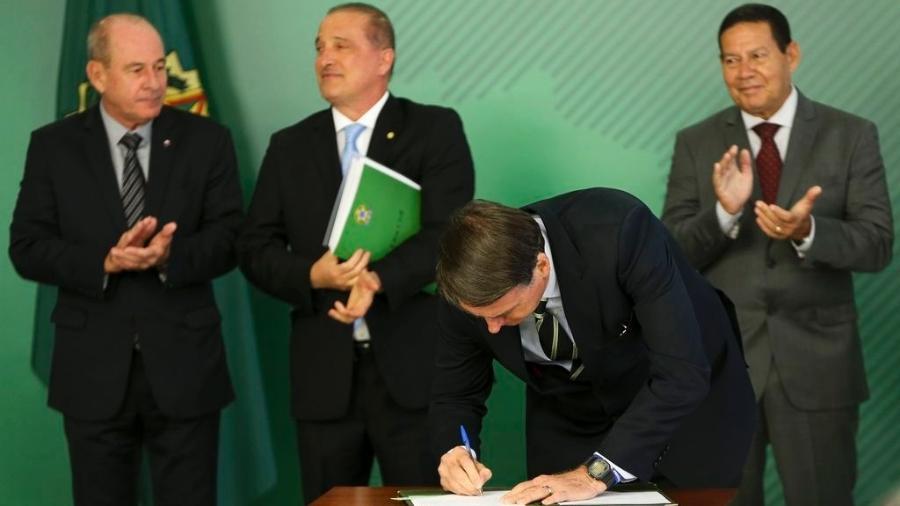O presidente Jair Bolsonaro comparou a caneta a uma arma, ao assinar o decreto que facilitou a posse de armas no Brasil - Marcelo Camargo/Agência Brasil