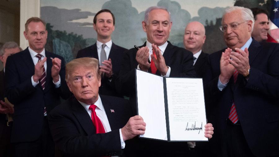 25.mar.2019 - Presidente dos EUA, Donald Trump, segura o documento no qual reconhece a soberania de Israel sobre as Colinas de Golã, ao lado do premiê israelense Benjamin Netanyahu - Saul Loeb/AFP