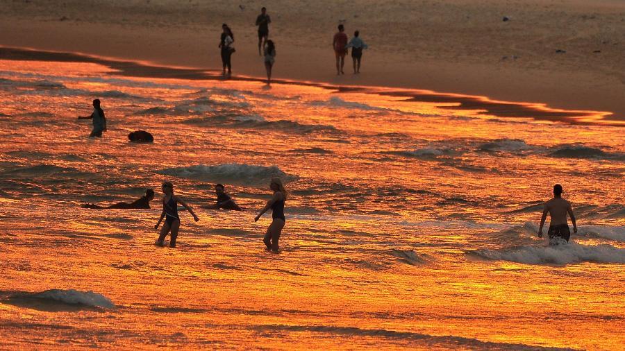 Australianos curtem praia durante por do sol em Sydney - Farooq Khan/AFP