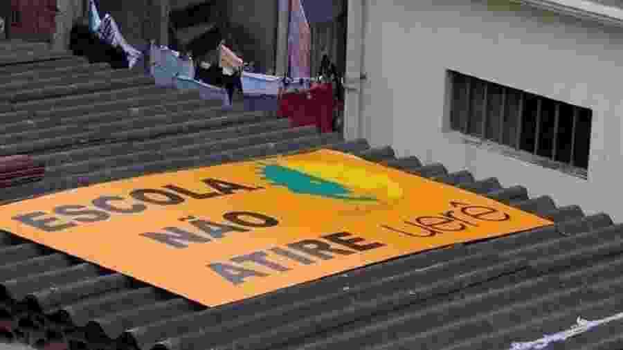 Projeto social no Complexo da Maré utilizou placa em teto de escola para protestar contra sobrevoos de helicópteros - Reprodução/Twitter/@renatasouzario