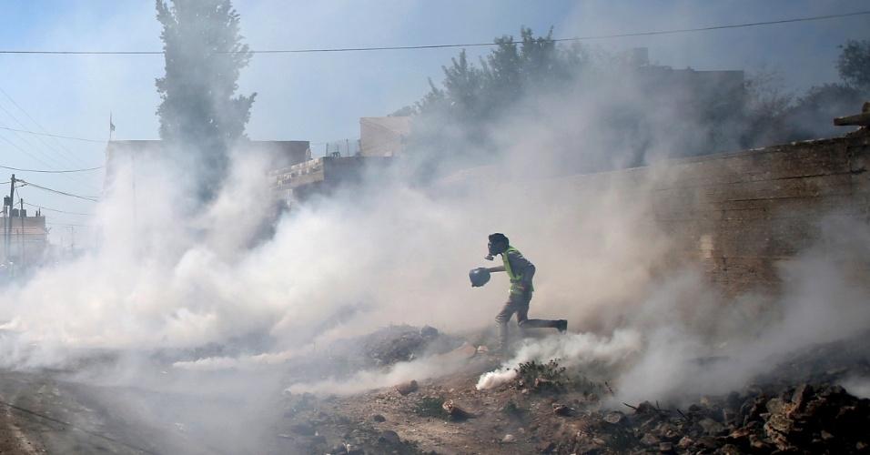24.jul.2015 - Em imagem desta sexta-feira (24), manifestante palestino caminha entre nuvens de gás lacrimogêneo disparados por soldados israelenses durante protesto na vila de Kufr Qadoom, perto da cidade de Nablus (Cisjordânia), contra a expansão de assentamentos israelenses em territórios comprovadamente palestinos