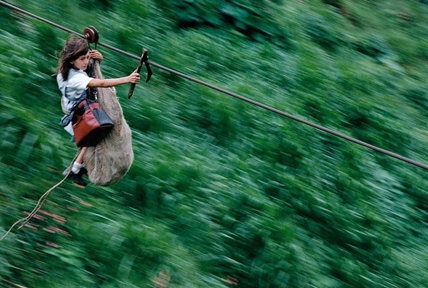 Colômbia - Crianças deslizam por um cabo de aço de 800 metros de comprimento e a 400 metros acima do rio Negro. Na foto, Daisy Mora carrega seu irmão de apenas 5 anos dentro de um saco para fazer a travessia