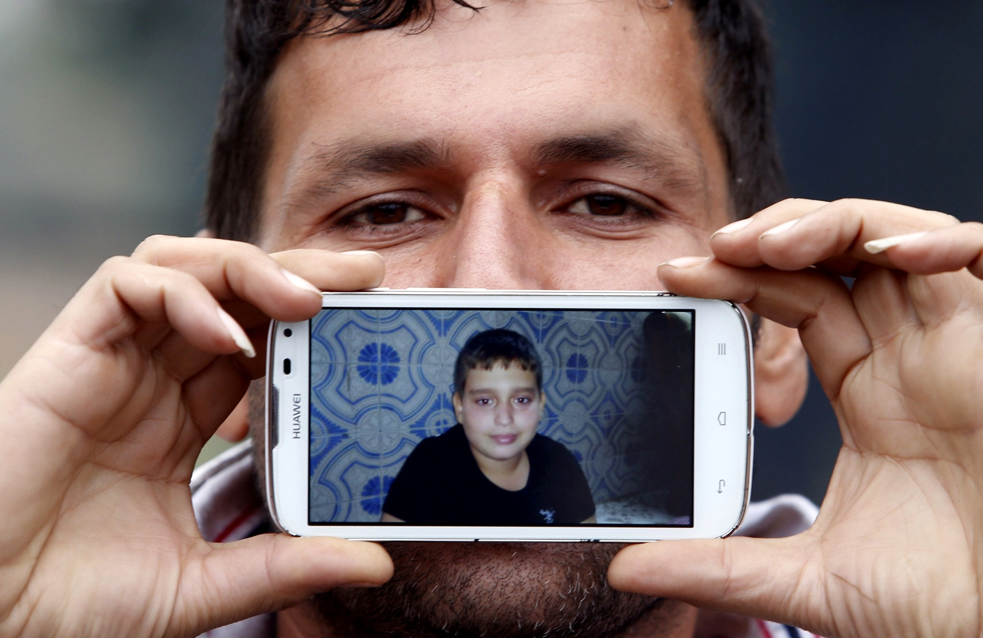 Said, de Teerã, no Irã, mostra uma imagem de seu filho Jospin enquanto aguarda para cruzar a fronteira da Eslovênia com a Áustria