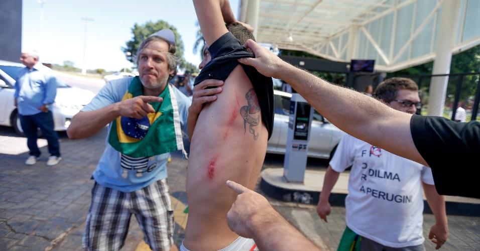 16.abr.2016 - Briga entre manifestantes pró-impeachment e seguranças do ex-presidente Lula em frente ao hotel Royal Tulip, em Brasília. Gritando palavras de ordem e com um inflável em formato de mortadela, eles seguiram o carro no qual Lula estava. Após a entrada do político, um carro branco que fechava o comboio parou na portaria e três seguranças à paisana desceram. Um deles trocou socos com um dos manifestantes