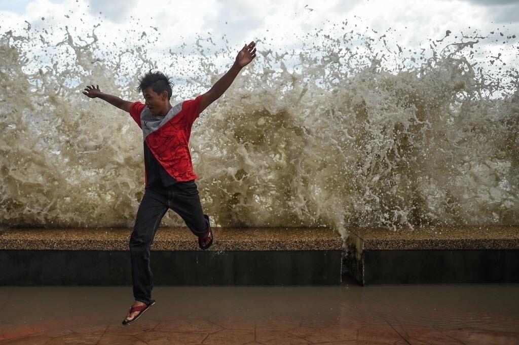 18.jul.2016 - Menino foge para não se molhar após onda bater na orla de Morib Beach, em Banting, na Malásia