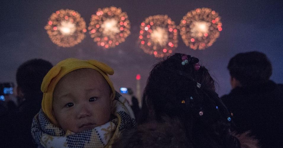 1.jan.2017 - Bebê é levado para acompanhar família na queima de fogos em Pyongyang, capital da Coreia do Norte