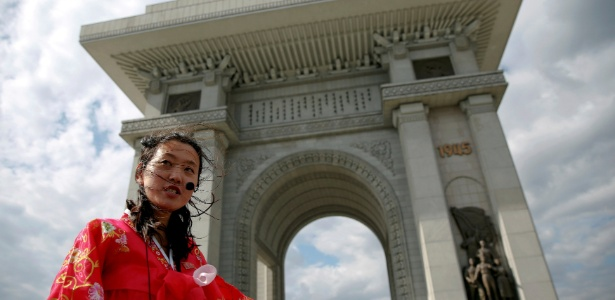 """4.mai.2016 - Guia de turismo apresenta o """"Arco do Triunfo"""" de Pyongyang aos visitantes, na Coreia do Norte"""