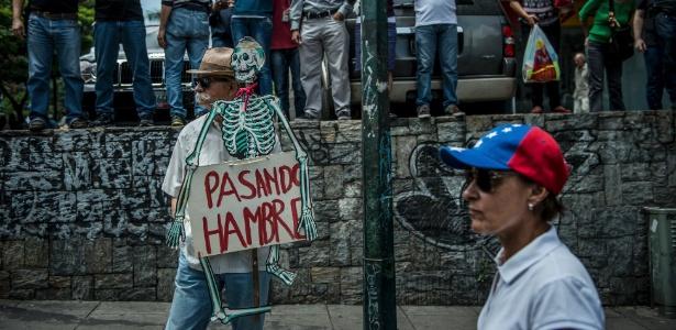 """22.mai.2017 - Gustavo Misle segura um cartaz na forma de esqueleto onde se lê """"passando fome"""", durante protesto contra o governo de Nicolás Maduro, em Caracas, Venezuela"""