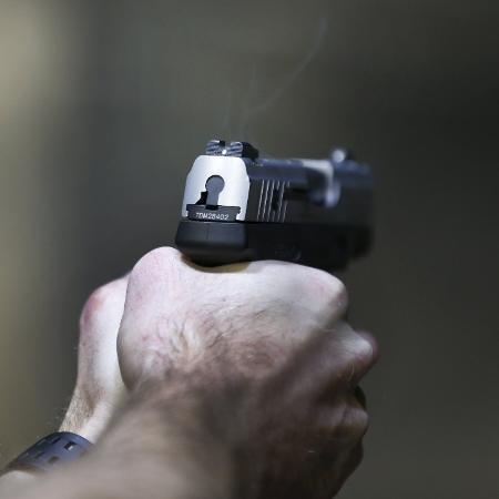 8.dez.2016 - Homem dispara uma Taurus Millenium 9mm em estande de tiro em Utah, EUA - George Frey/ Reuters