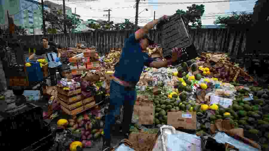 11.fev.2020 - Permissionários da Ceagesp, na zona oeste da capital, descartam alimentos após as fortes chuvas que atingiram a cidade na segunda-feira - Felipe Rau/Estadão Conteúdo