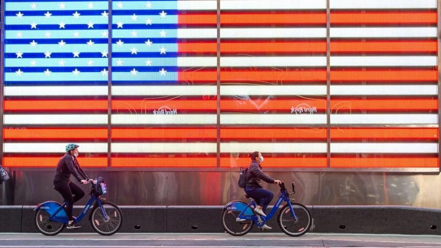 De máscara, ciclistas passeiam pela Times Square, famosa avenida de Nova York, nos EUA - Noam Galai/Getty Images