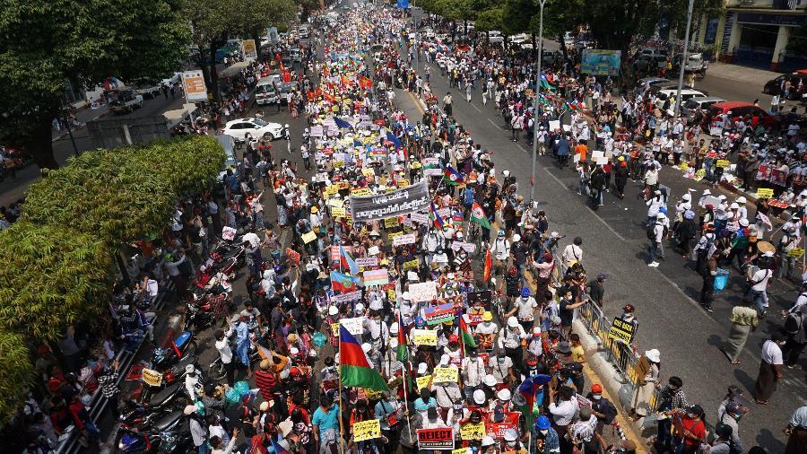 Manifestantes seguram cartazes e marcham em protesto contra golpe militar em Yangon, Mianmar - Sai Aung Main/AFP