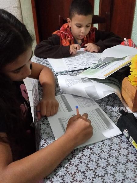 Os irmãos, Vitória e Lucas, estudam com materiais impressos disponibilizados pela escola - Arquivo pessoal