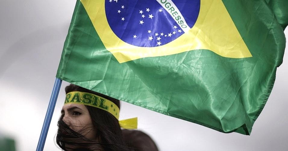13.dez.2015 - Manifestante carrega a bandeira do Brasil durante um protesto pedindo o impeachment da presidente Dilma Rousseff, perto do Congresso Nacional, em Brasília