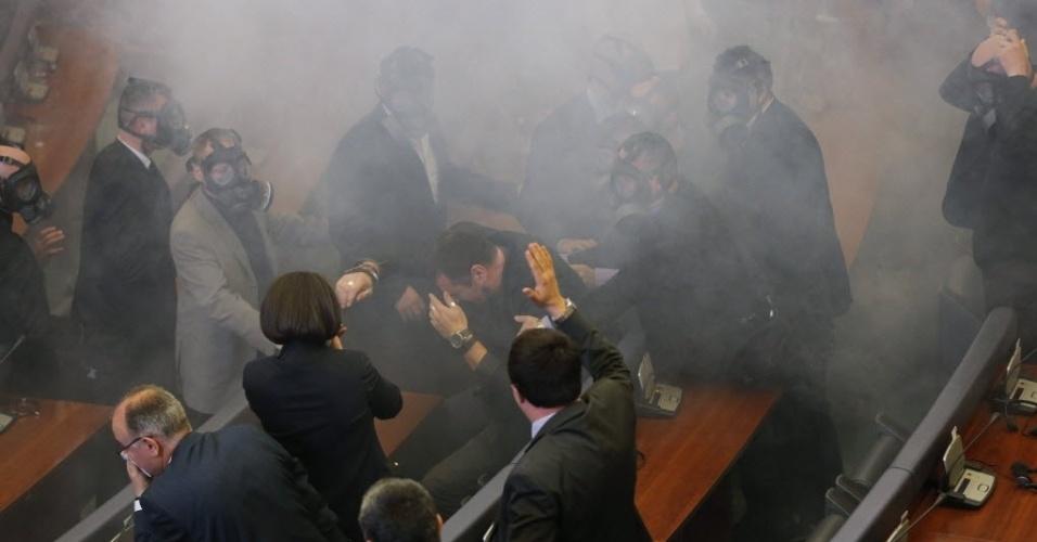 19.fev.2016 - Seguranças usam máscaras para retirar uma bomba de gás lacrimogêneo que foi lançada por deputados opositores durante uma sessão plenária do Parlamento do Kosovo. A oposição ultranacionalista protestou novamente contra a normalização de relações com a Sérvia, de quem a região de separou em 2008