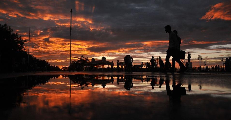 18.ago.2016 - Pedestres caminham durante belo fim de tarde na cidade de Shimla, na Índia. O dia foi marcado por uma forte tempestade, mas terminou com este lindo céu