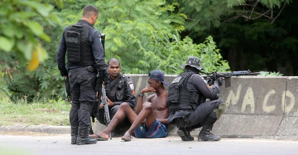 1º.fev.2018 - Policiais militares e um homem não identificado se agacham atrás da mureta da Linha Amarela, na zona oeste do Rio de Janeiro. Troca de tiros entre PMs e criminosos fechou a via pelo 2º dia seguido