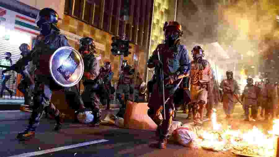 2.nov.2019 - Polícia passa por barricada de fogo em protesto contra o governo em Hong Kong - Thomas Peter/Reuters